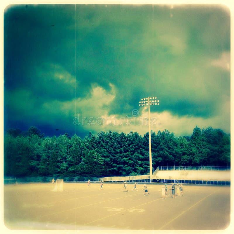 在曲棍网兜球领域的多云天空 免版税库存照片