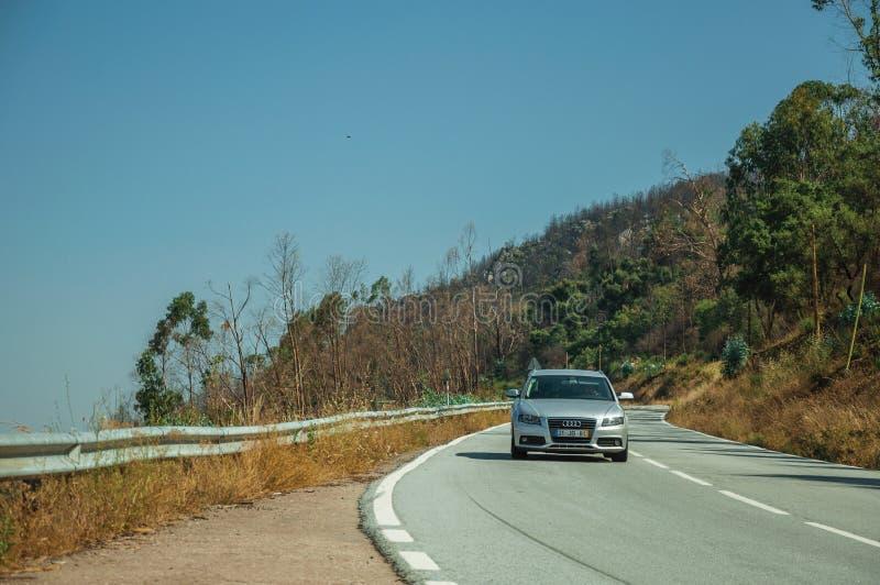 在曲线路的汽车通过多小山风景 库存图片
