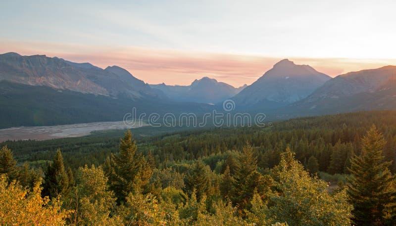 在更低的两Medicine湖的充满烟雾的日落在蒙大拿美国durng的冰川国家公园2017秋天火 库存图片