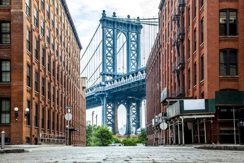 在曼哈顿和布鲁克林之间的曼哈顿大桥在从一个狭窄的胡同看见的East河附寄由在a的两栋砖瓦房 免版税图库摄影