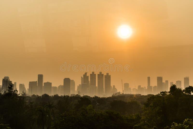 在曼谷市SkylineHigh大厦上的日出在公园后 免版税库存图片