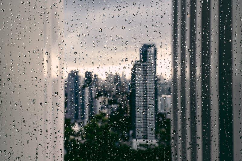 在曼谷的雨:在焦点外面在玻璃窗后的都市风景与雨下降 免版税库存照片