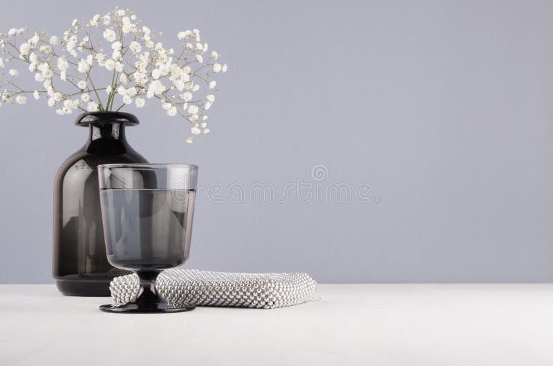 在最低纲领派样式的典雅的装饰梳妆台-有花的黑花瓶,玻璃,化妆辅助部件变成银色在灰色墙壁上的袋子 库存图片