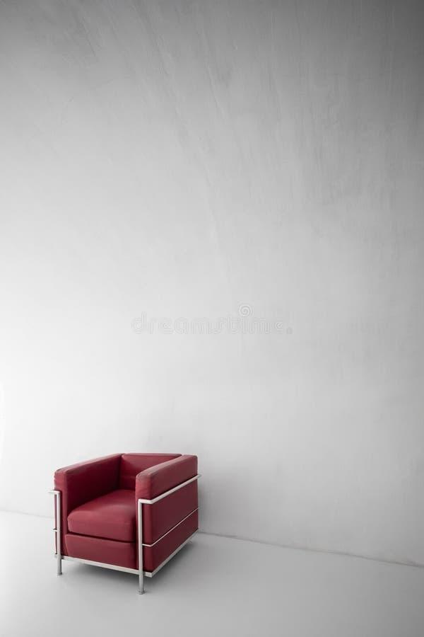 在最低纲领派内部的红色扶手椅子 免版税图库摄影