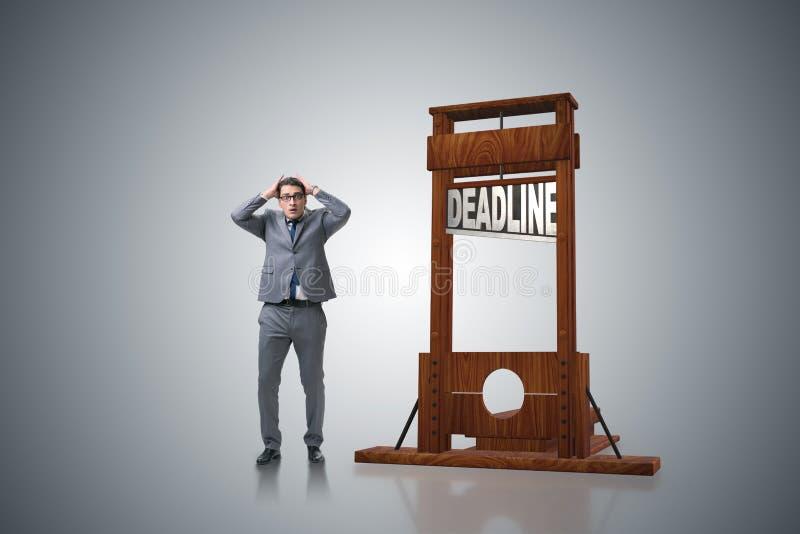 在最后期限概念的商人与断头台 免版税图库摄影