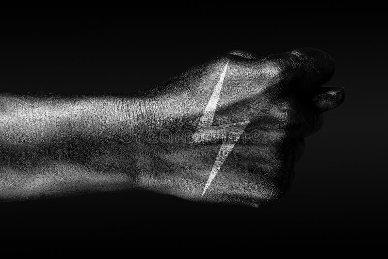 在有一个拉长的闪电标志的一只手上,无花果被描述,能量,电,危险的标志,在黑暗的背景 免版税库存照片
