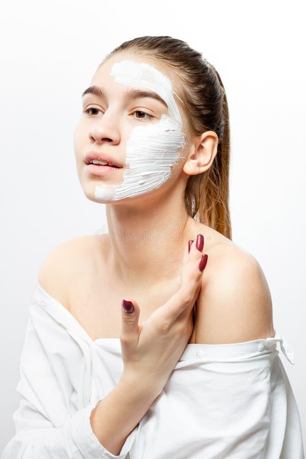 在有一个白色化妆面具的白色衣裳打扮的年轻女人在一半她的面孔握她的手在她的肩膀  免版税库存照片
