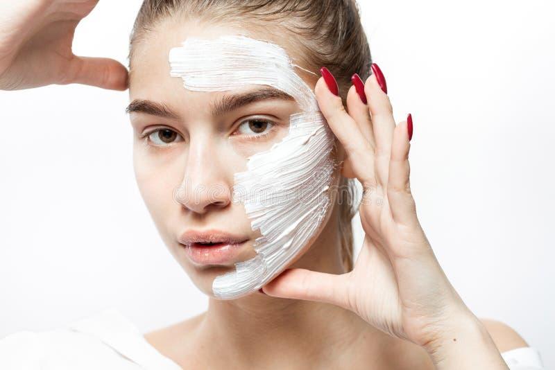 在有一个白色化妆面具的白色衣裳打扮的年轻女人 免版税库存照片