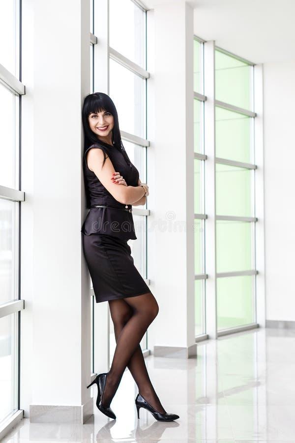 在有一个短裙身分的一套黑西装打扮的年轻美丽的愉快的深色的妇女在窗口附近在办公室, 免版税库存照片