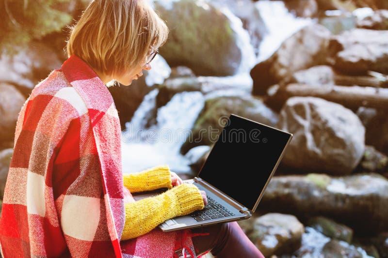 在有一台膝上型计算机的格子花呢披肩格子花呢披肩包裹的女孩的大模型图象有在她的膝部的一个空白的黑桌面的反对 免版税库存图片