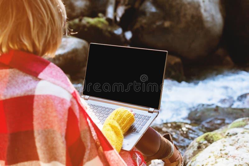 在有一台膝上型计算机的格子花呢披肩格子花呢披肩包裹的女孩的大模型图象有在她的膝部的一个空白的黑桌面的反对 图库摄影