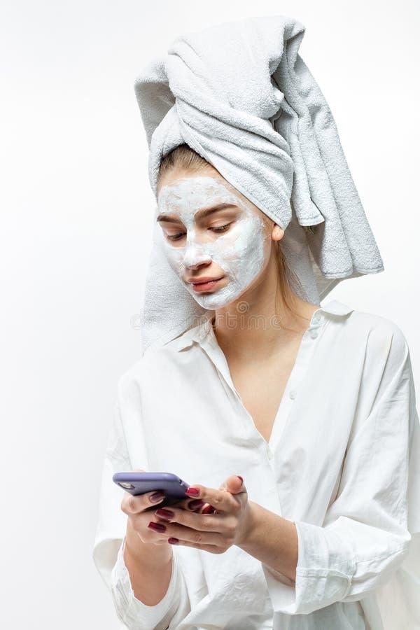 在有一块白色毛巾在她的头发和化妆面具的白色衣裳打扮的美丽的年轻女人在她的面孔对负流动 免版税库存图片
