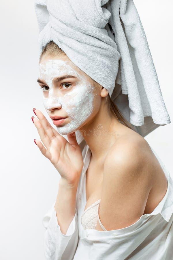 在有一块白色毛巾的白色衣裳打扮的美丽的年轻女人在她的头发在她的面孔上把一个化妆面具放 库存图片
