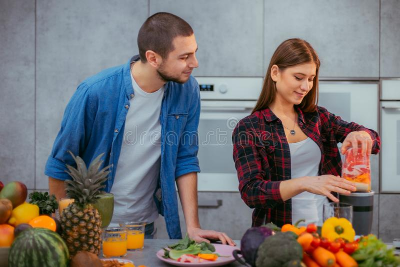 在有一对美好的设计夫妇的一个现代厨房里使用一起做一名健康圆滑的人的搅拌器的早晨 免版税图库摄影