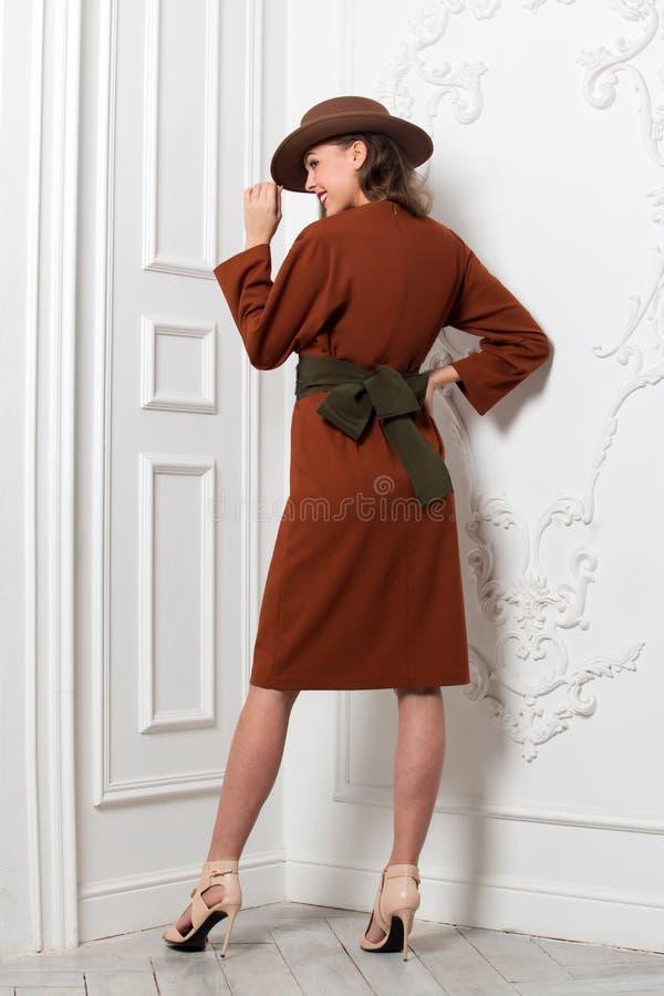 在有一条宽传送带和一个棕色帽子的棕色礼服打扮的时兴的迷人的女孩摆在对白色墙壁在屋子里 免版税库存图片