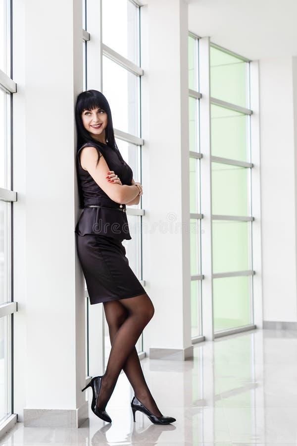 在有一条短裙的一套黑西装打扮的年轻可爱的愉快的深色的妇女在白色的窗口附近站立 库存图片