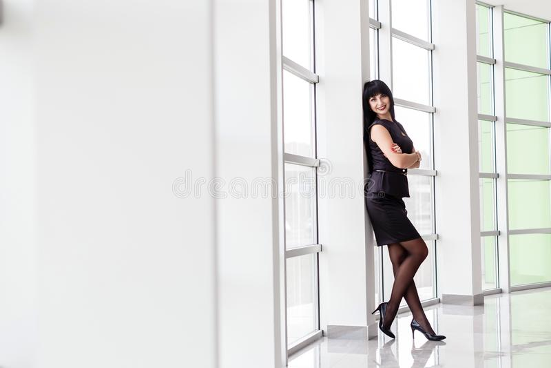 在有一条短裙的一套黑西装打扮的年轻可爱的愉快的深色的妇女在窗口附近站立在办公室, 免版税库存照片