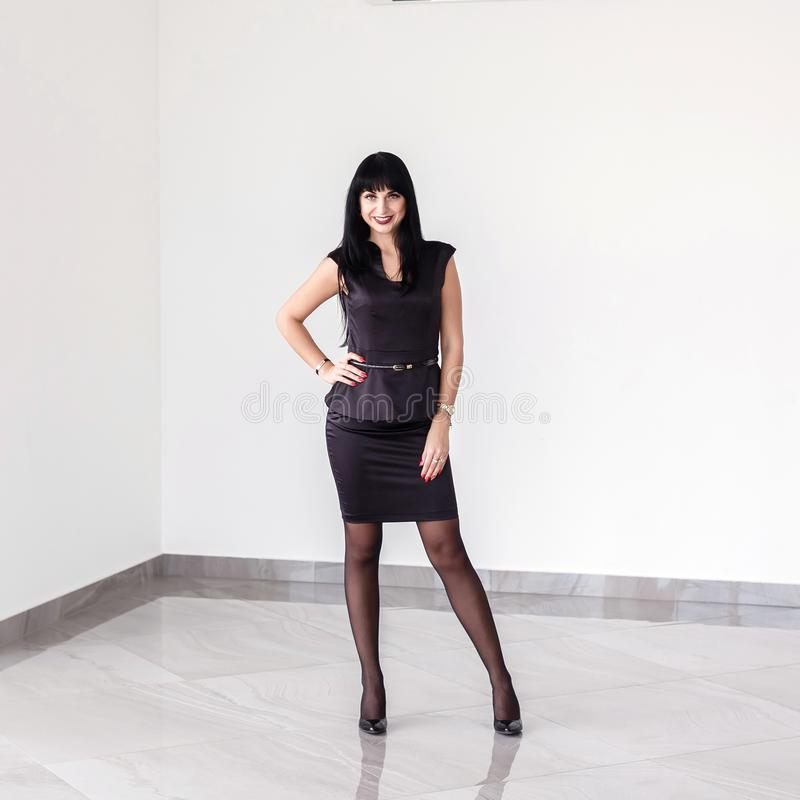 在有一条短裙的一套黑西装打扮的年轻可爱的愉快的深色的妇女站立对白色墙壁  免版税库存照片