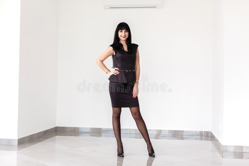 在有一条短裙的一套黑西装打扮的年轻美丽的愉快的深色的妇女站立对白色墙壁  图库摄影