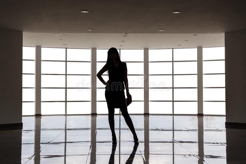 在有一条短裙的西装打扮的年轻可爱的妇女剪影站立反对在a的大空的窗口 免版税库存图片