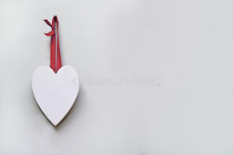 在有一条红色丝带的简单的墙壁上垂悬的白色木被雕刻的心脏 免版税库存照片