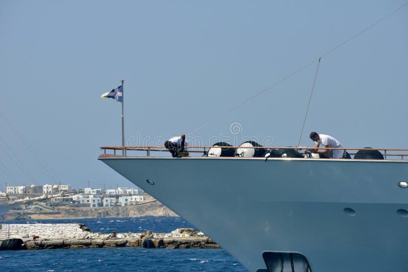 在有两位水手人工作的米科诺斯岛港口停泊的白色游艇弓 免版税库存图片