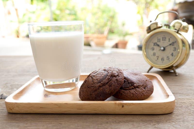 在有乳白玻璃的一块木板材安置的自创软的黑暗的巧克力果仁巧克力曲奇饼在木桌上 在曲奇饼后有金子vi 免版税图库摄影