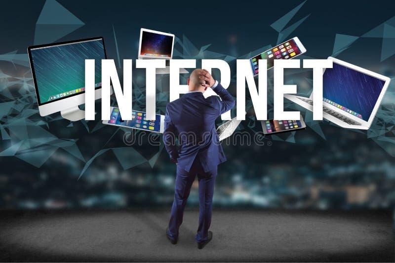 在有互联网标题的被围拢的墙壁前面的商人  库存图片