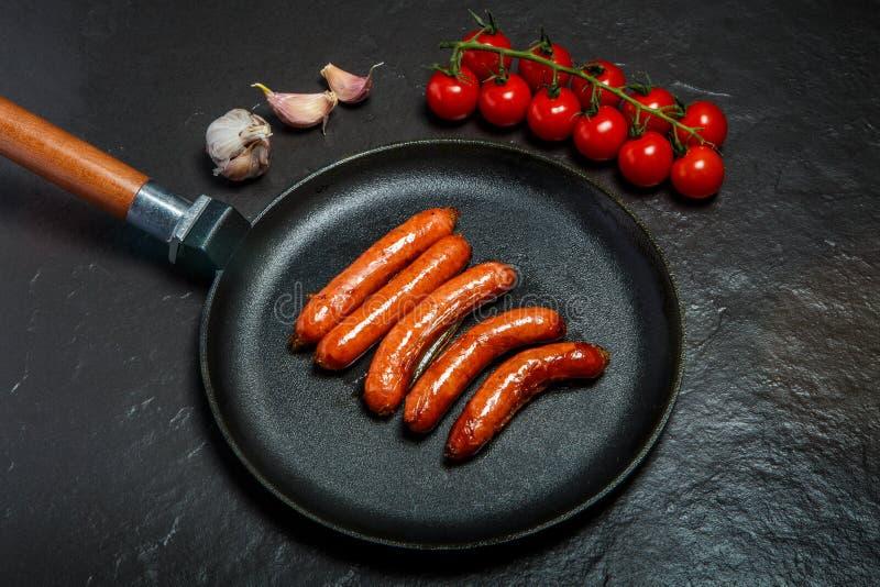 在有五短小的油煎的圆的平底锅的顶视图寻找香肠 库存照片
