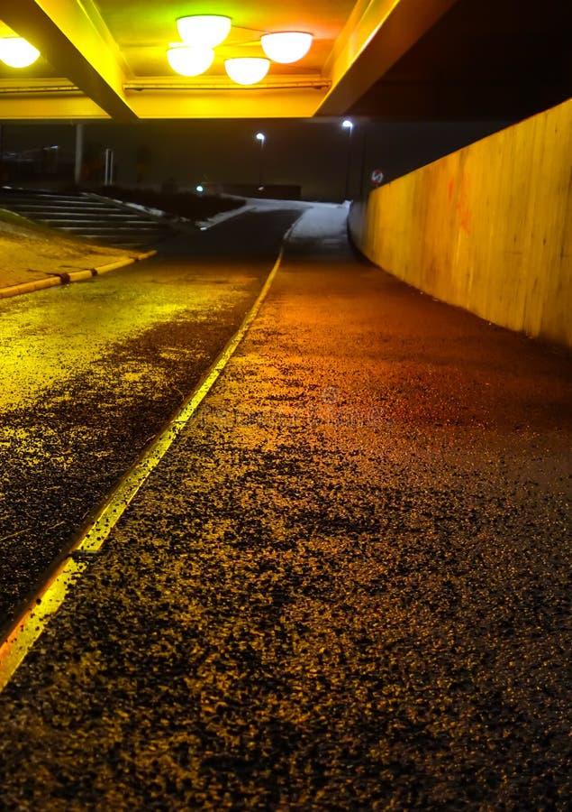 在有五颜六色的光反射的都市桥梁下在路 图库摄影