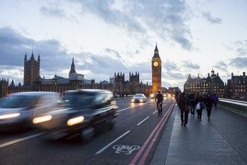 在有人和汽车的中央伦敦市交易 大本钟在背景,照片中被拍晚上 免版税库存照片