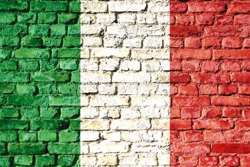 在有传统绿色,白色和红颜色的一个砖墙上绘的意大利国旗 库存照片