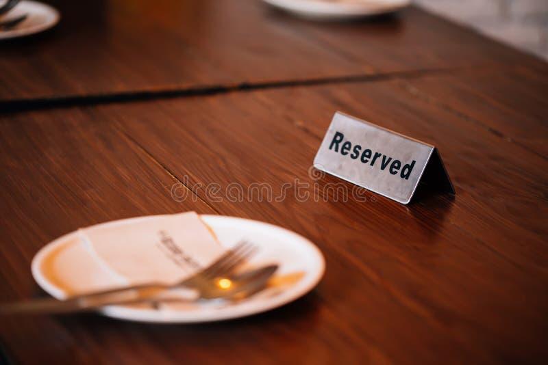 `在有匙子、叉子和板材的餐馆预留了在餐桌上的`标志 免版税库存照片