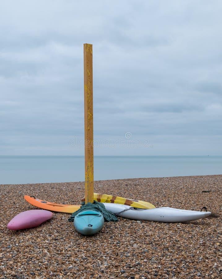 在有卵石花纹的海滩的五颜六色的独木舟在Hove,东萨塞克斯郡,英国 拍摄在一个冷,镇静冬日 免版税图库摄影