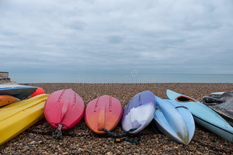在有卵石花纹的海滩的五颜六色的独木舟在Hove,东萨塞克斯郡,英国 拍摄在一个冷,镇静冬日 库存图片