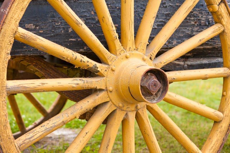 在有历史的购物车的老被绘的黄色马车车轮 免版税库存图片