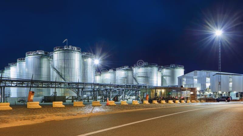 在有启发性石油化学的生产设备夜间的,安特卫普,比利时港的巨型的筒仓  库存图片
