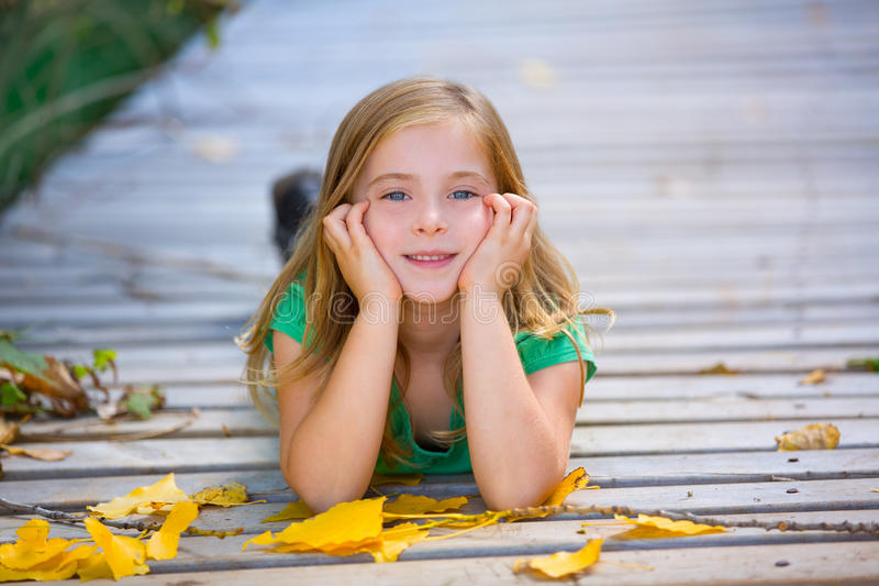 在有室外黄色的叶子的秋天木甲板哄骗女孩 库存图片