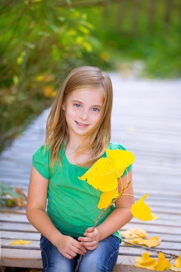 在有室外黄色的叶子的秋天木甲板哄骗女孩 免版税库存图片