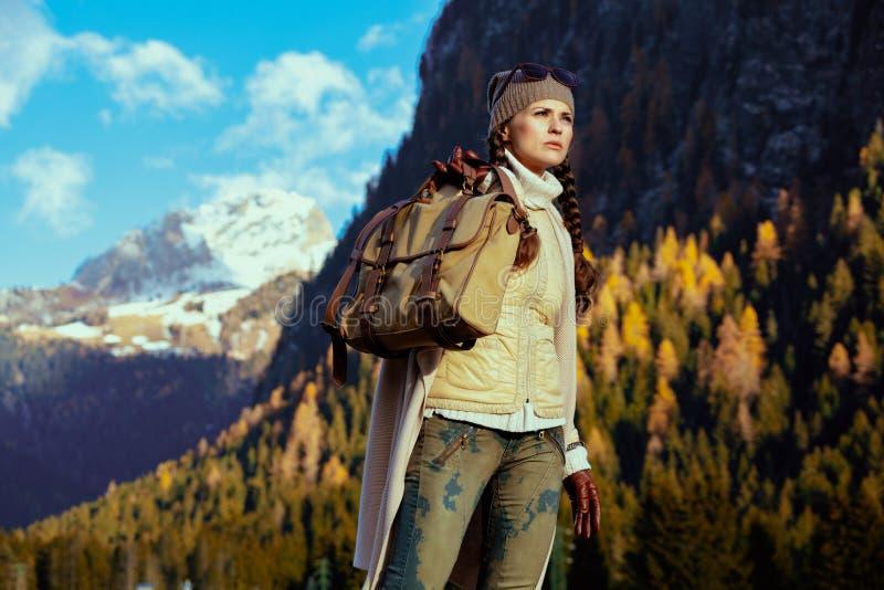 在有山的风景前面的妇女徒步旅行者徒步游览 免版税库存照片