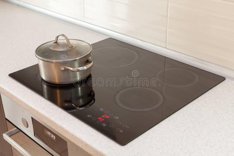 在有归纳火炉的现代厨房里金属化钢平底深锅 免版税库存照片