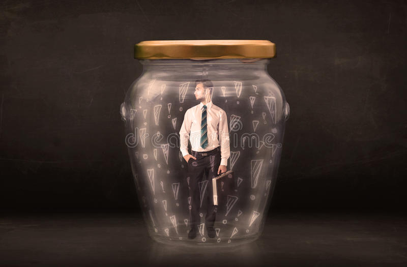 在有惊叹号概念的瓶子困住的商人 免版税库存照片