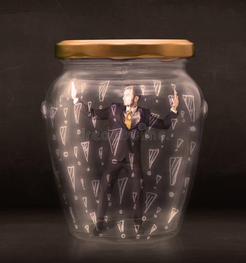 在有惊叹号概念的瓶子困住的商人 库存图片