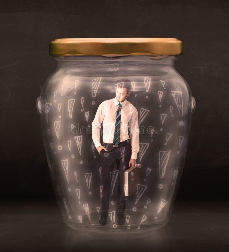 在有惊叹号概念的瓶子困住的商人 免版税库存图片