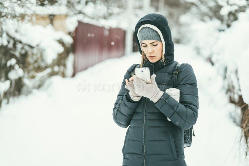 在有手机和热水瓶烧瓶的一件黑冬天夹克打扮的美女在她的胳膊下 美丽的目的地横向滑雪雪 免版税库存照片