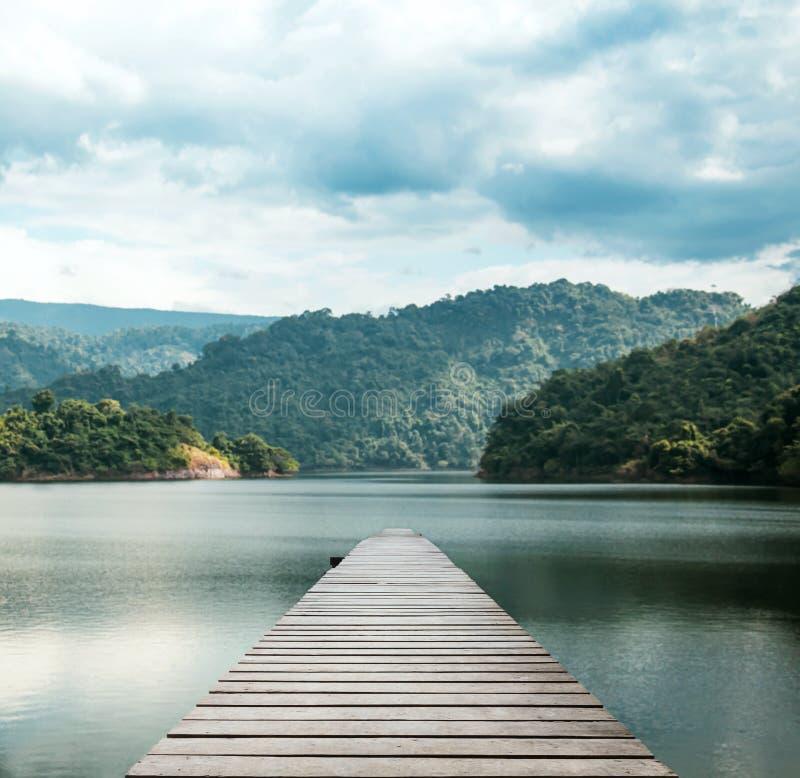 在有旅行旅游业与热带森林海岛和阳光的步行方式与美丽的天空的海的木桥梁 免版税库存照片