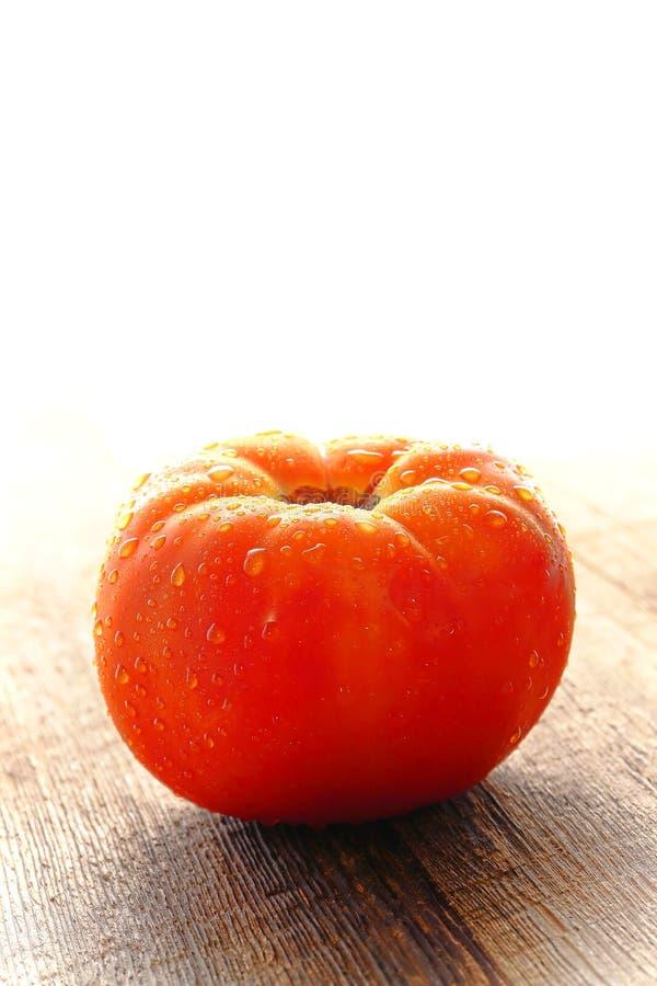 在有机红色牛排蕃茄的露水在木表 图库摄影