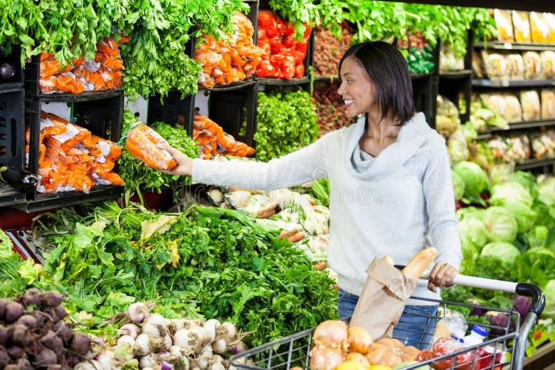 在有机部分的妇女买的红萝卜 图库摄影