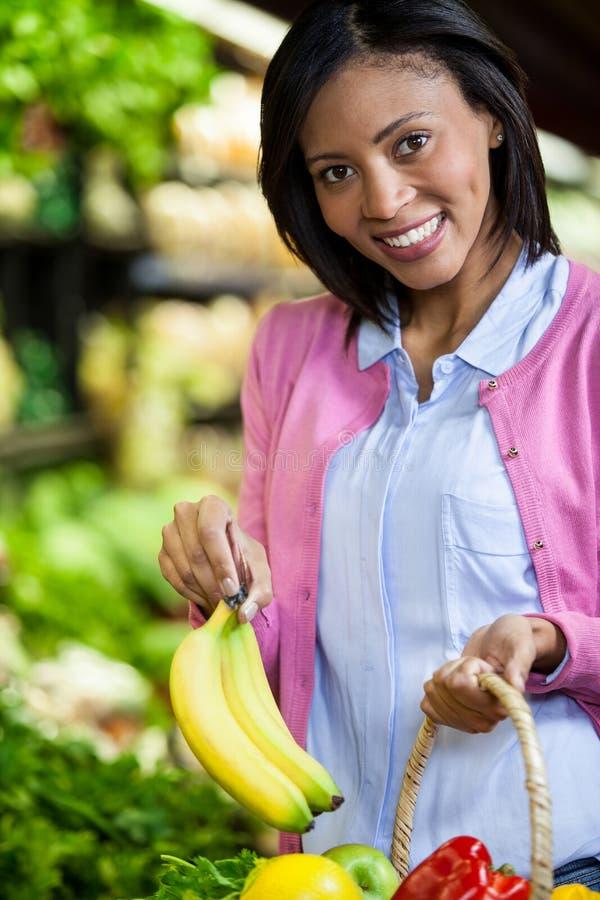 在有机部分的妇女买的香蕉 免版税库存图片