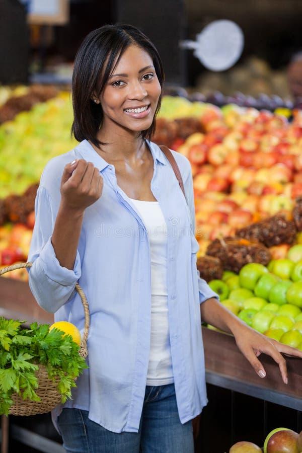 在有机部分的微笑的妇女买的果子 图库摄影